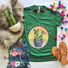 flatlay of green unisex fit tee with cactus print and stay prickly in front center