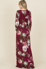 back view of long sleeve burgundy and floral long mazi dress. super soft and stretchy material cinched at the small of your waist. beautiful eye catching burgundy color. and has pockets