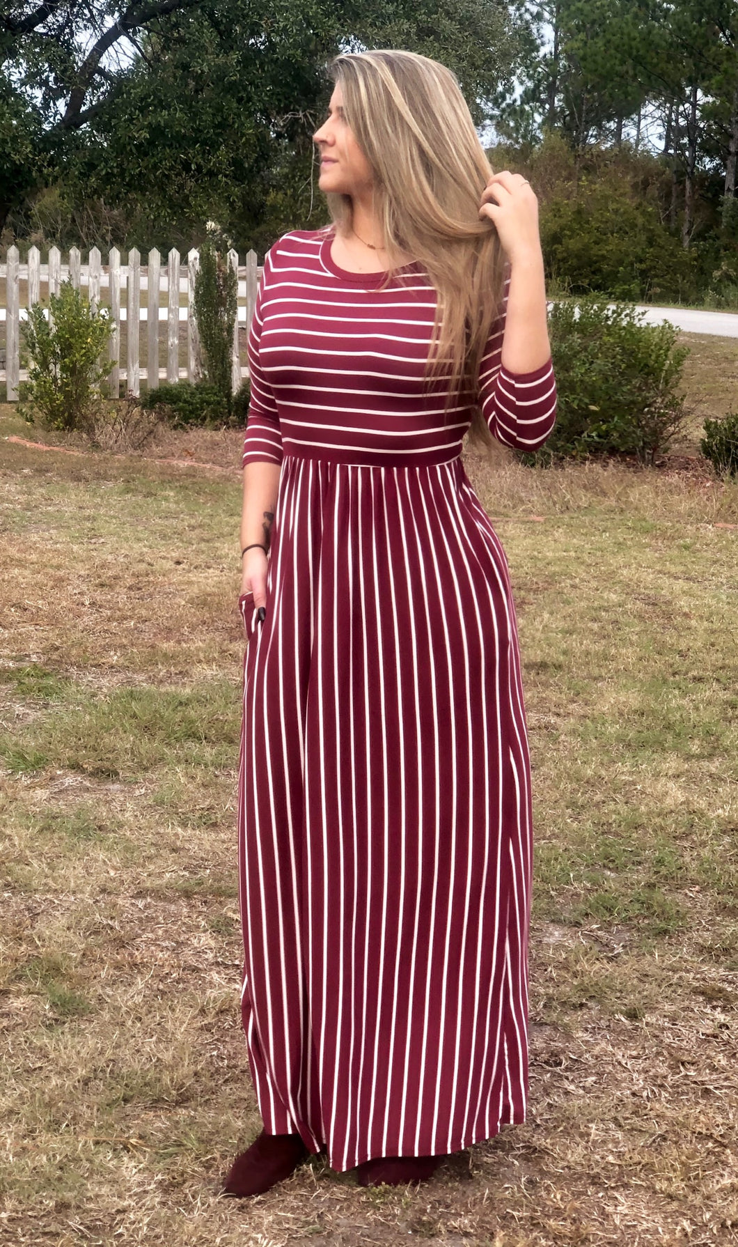 full body view of 3/4 quarter sleeve burgundy and white two directional stripes long maxi dress. cinches at the small of the waist. perfect for shorter and taller people with its stretchy and soft material