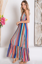 side view of mulit-color stripe serape maxi with adjustable spaghetti strapes, smocked waist, and ruffle hem