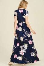back view of Navy and floral print short sleeve long maxi with soft and stretchy material, scoopneck, and pockets
