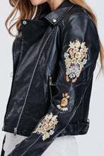 zoomed in side view of sleeve on faux leather jacket with embroidered sleeves. meets at your waist. zip up in front and tie around waist