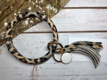 large print leopard animal print with white background bangle ring keychair with tassle and monogram tag. large ring for any size wrist and easy clip for attaching keys. contains two 2 rings to attach keys to. leopard print, animal print, cute, and fun.