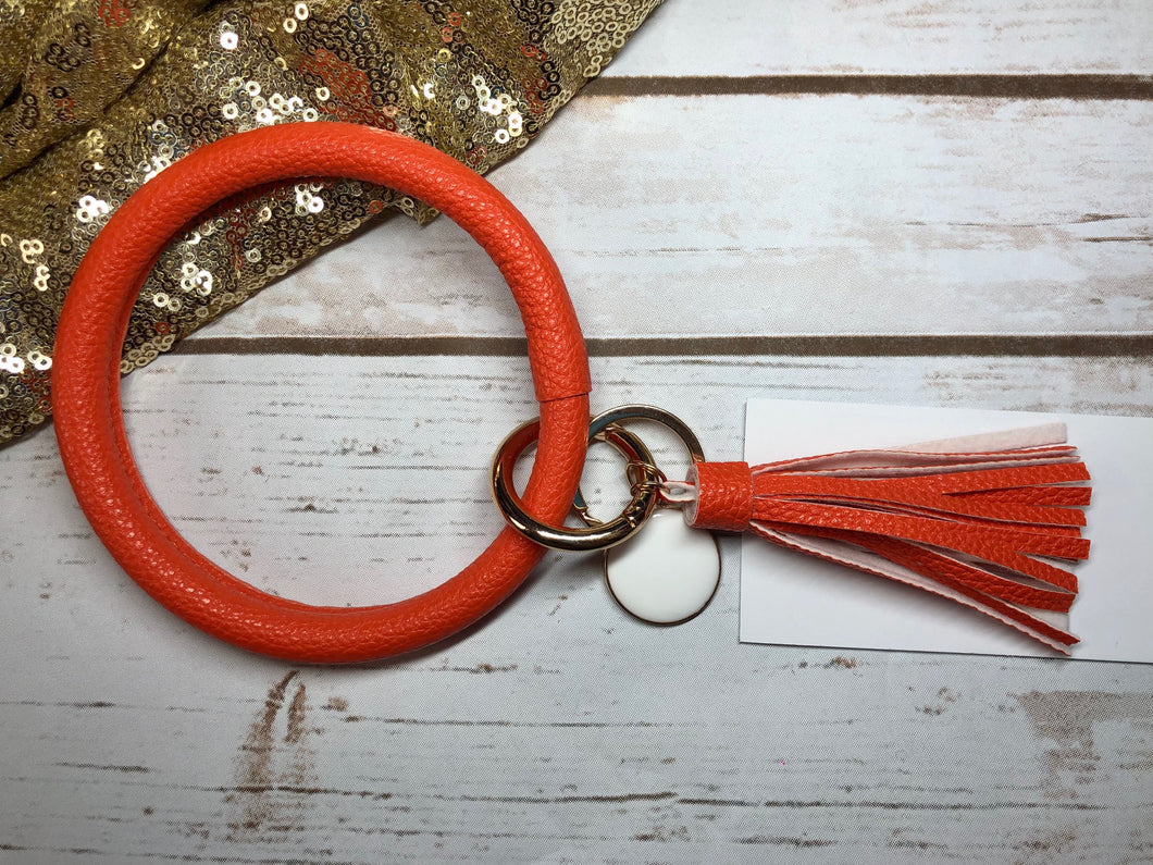 orange bangle ring keychair with tassle and monogram tag. large ring for any size wrist and easy clip for attaching keys. contains two 2 rings to attach keys to. monochromatic, cute, and fun.