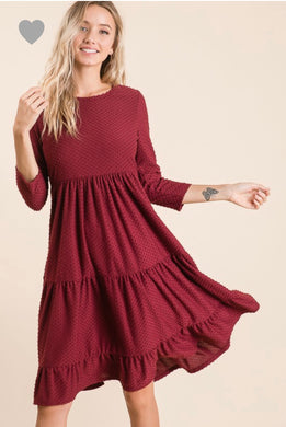 short sleeve burgundy with dot textured short dress that goes to knees. cinches at the small of the waist and flows out tiered on the bottom half