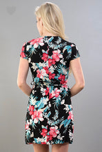 back view of short sleeve short wrap dress with black, coral, and blue contrast floral print. ties in front or side and has pockets