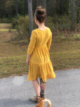 back view of short sleeve mustard with dot textured short dress that goes to knees. cinches at the small of the waist and flows out tiered on the bottom half