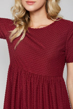 up close view of detail on short sleeve burgundy with dot textured short dress that goes to knees. cinches at the small of the waist and flows out tiered on the bottom half