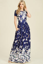 Navy ombre floral short sleeve long maxi dress with white floreal print heavy on top and bottom and faded in middle like falling flowers. scoopneck and pockets
