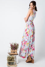 side view of pale mint and floral print pattern long maxi dress with sleeveless top. cinched at small of wasit and has pockets
