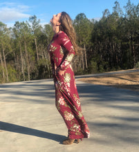 side view of long sleeve burgundy and floral long mazi dress. super soft and stretchy material cinched at the small of your waist. beautiful eye catching burgundy color. and has pockets