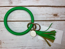 green bangle ring keychair with tassle and monogram tag. large ring for any size wrist and easy clip for attaching keys. contains two 2 rings to attach keys to. monochromatic, cute, and fun.