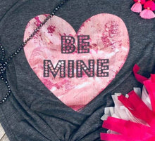 large zoomed in picture of short sleeve charcoal grey gray tee with large pink foil heart in middle with be mine in large print within pink foil heart. womens fit with V neck. perfect lounging shirt or to tie the bottom and pair with jeans and booties
