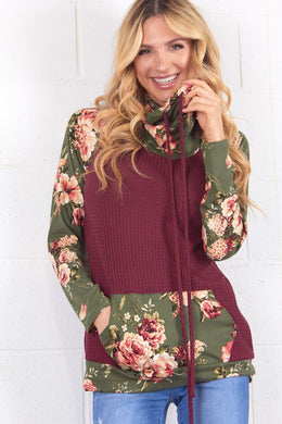 burgendy and olive floral long sleeve top. Sleeves, loose neckline, and front pouch are olive green with floral accent