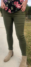up close picture of olive green moto jeggings with real back pockets and an elastic waistband. can be worn everyday casual or with a dressy top and heels. S/M fit- 2-6. M/L fit- 8-10