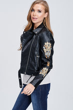 side view of faux leather jacket with embroidered sleeves. meets at your waist. zip up in front and tie around waist