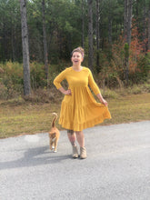 short sleeve mustard with dot textured short dress that goes to knees. cinches at the small of the waist and flows out tiered on the bottom half