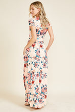 back view of Short sleeve soft blush and floral print long maxi dress. Scoopneck and has pockets
