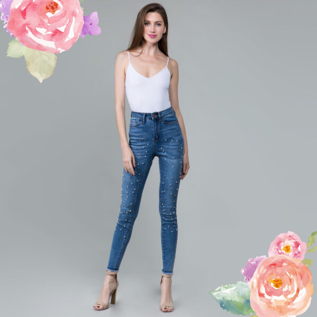 blue high rise skinny jeans with stretch. fully embellished in silver and white pearls down to fray hem detail