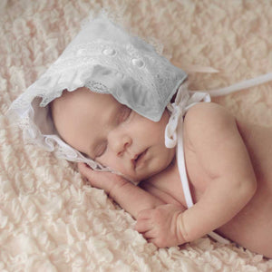 Baby sleeping wearing white ribbon baby bonnet.