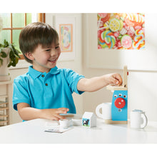 Child using toy coffee set.
