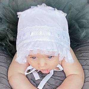 Top view of baby wearing White Ribbon Baby Bonnet.