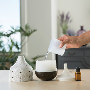 Adding water to essential oil diffuser.