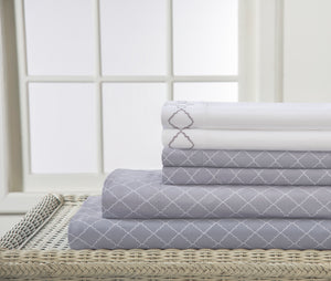 Gray Bed sheets with white pillowcases.