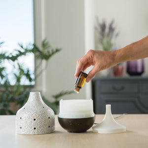 Adding essential oil to diffuser.