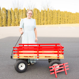 Large red wagon with woman standing next to wagon