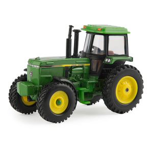 Toy vintage John Deere tractor with cab.