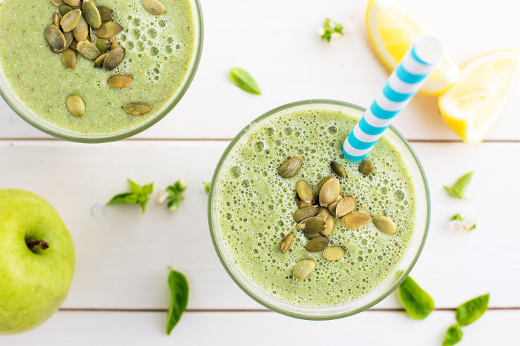 Smoothie with pumpkin seeds, green apple, fresh basil, cucumber, and lemon.