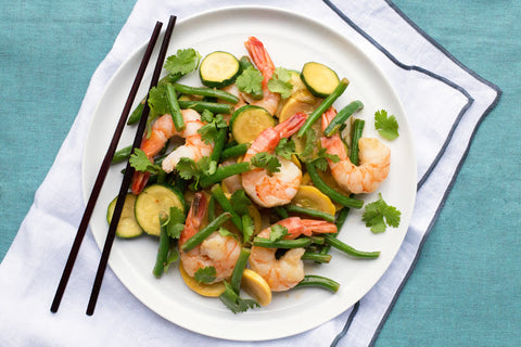 Close up of shrimp over green beans with zucchini, yellow squash, and cilantro.