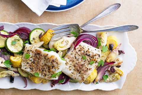 Baked cod with olives, artichoke hearts, zucchini, squash, and red onions.