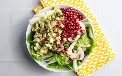 Close up of egg salad over romaine with mushrooms and pomegranate seeds.