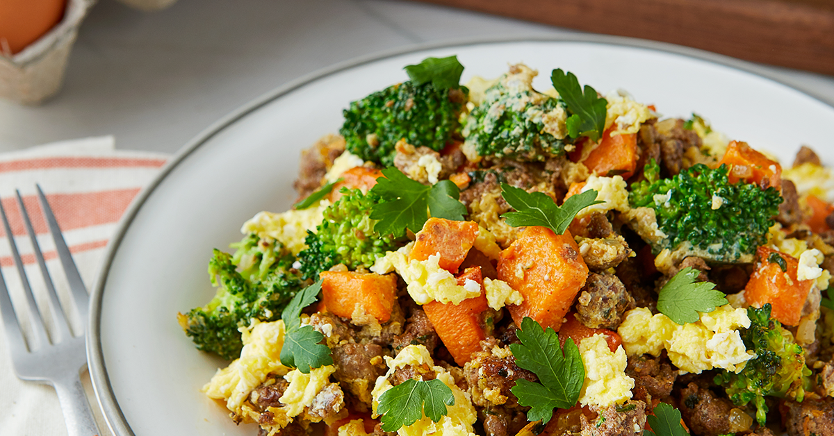 Close up of spiced lamb scramble with sweet potatoes, eggs, broccoli, and parsley.