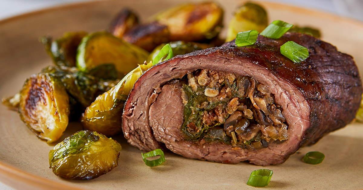 Flank steak stuffed with spinach, mushrooms and onions with a side of Brussels sprouts.