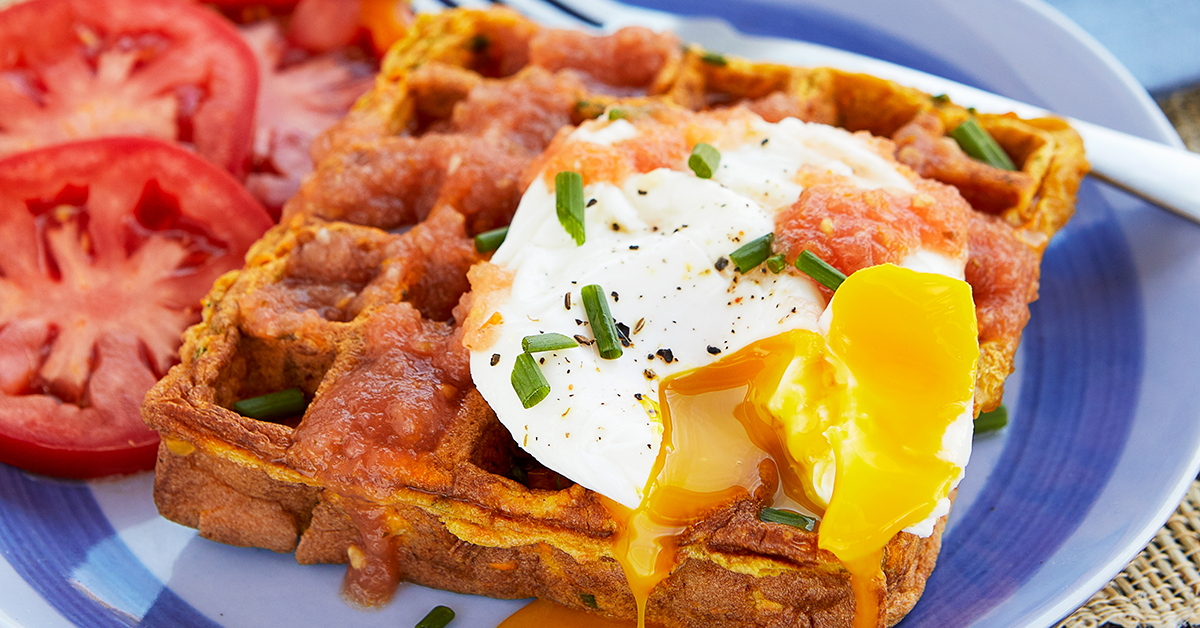 Close up of waffle made with sweet potatoes with a poached egg on top.