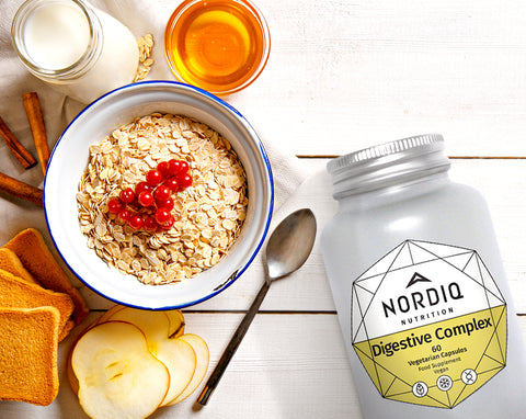 NORDIQ Nutrition Digestive Complex bottle and bowl of oatmeal with spoon and apples.