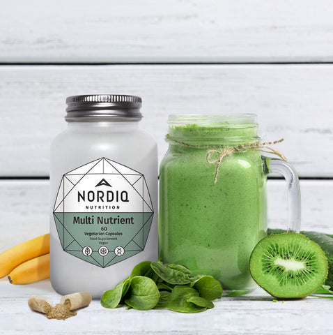 NORDIQ Nutrition Multi Nutrient bottle with green smoothie and kiwi, spinach leaves, banana, and open capsule.