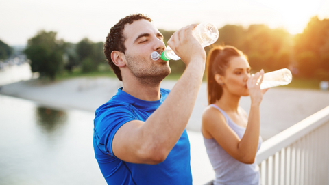 Man and woman drinking a bottle of water while on a run.