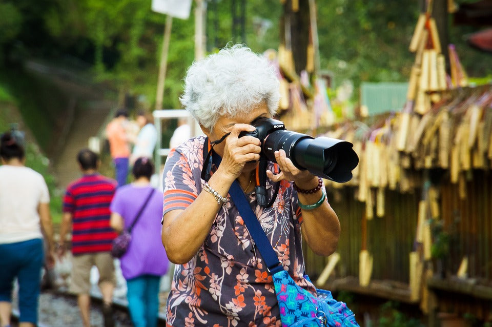 old woman taking picture outdoors
