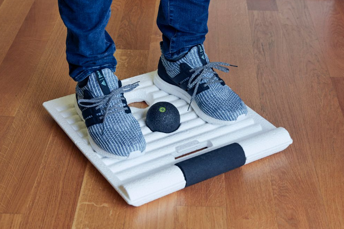 Close up of man standing on SMART MOVE BOARD with featured foam rolling tools.