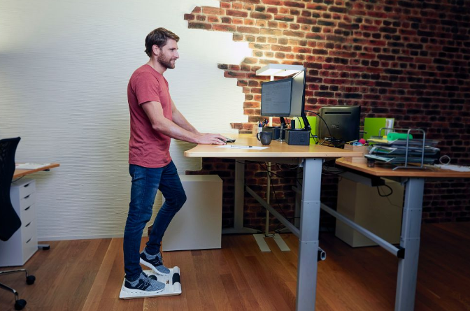 Man standing on BLACKROLL Smart Move Board at standing desk.
