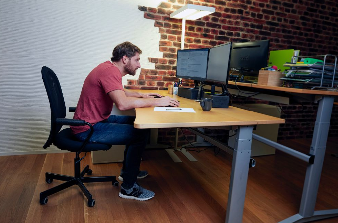Man hunching at desk on computer.
