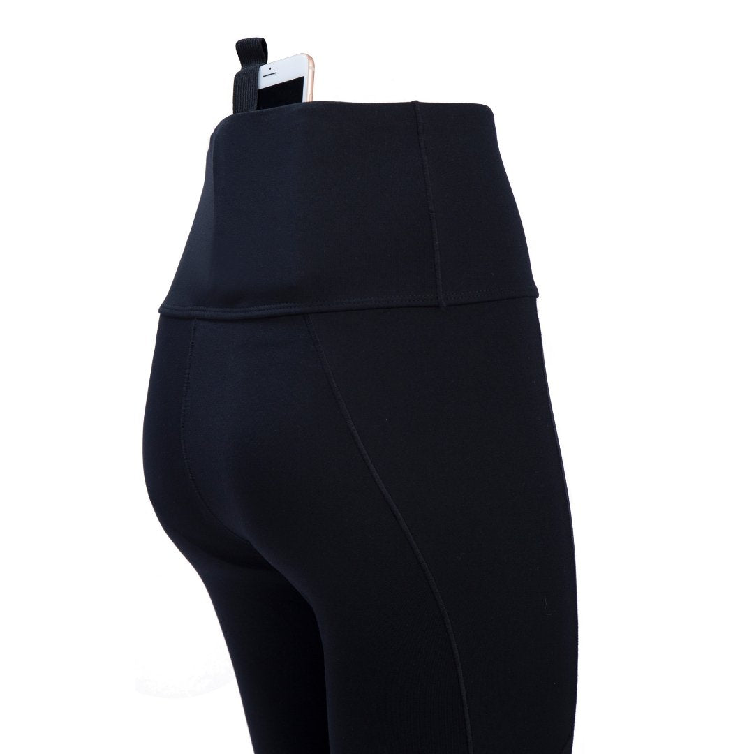 side-view of black concealed carry leggings with cell phone strapped in place