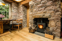 wood burning stove set in stone wall