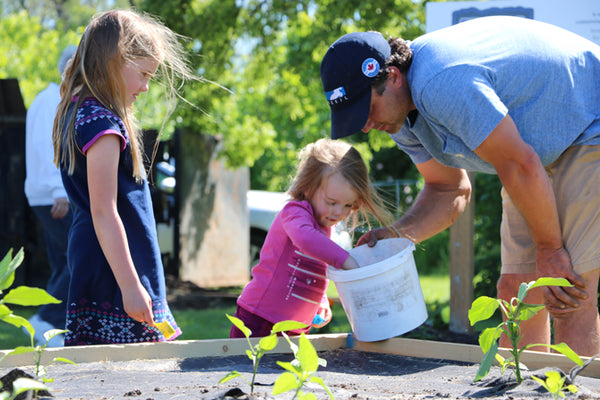 Jordan Elliott of Marine Recycling Corporation shows a youngster how to plant seedlings at the Lockview Park Community Garden in Port Colborne in support of the Port Cares Food Bank.