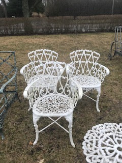 four white metal chairs   (outside)