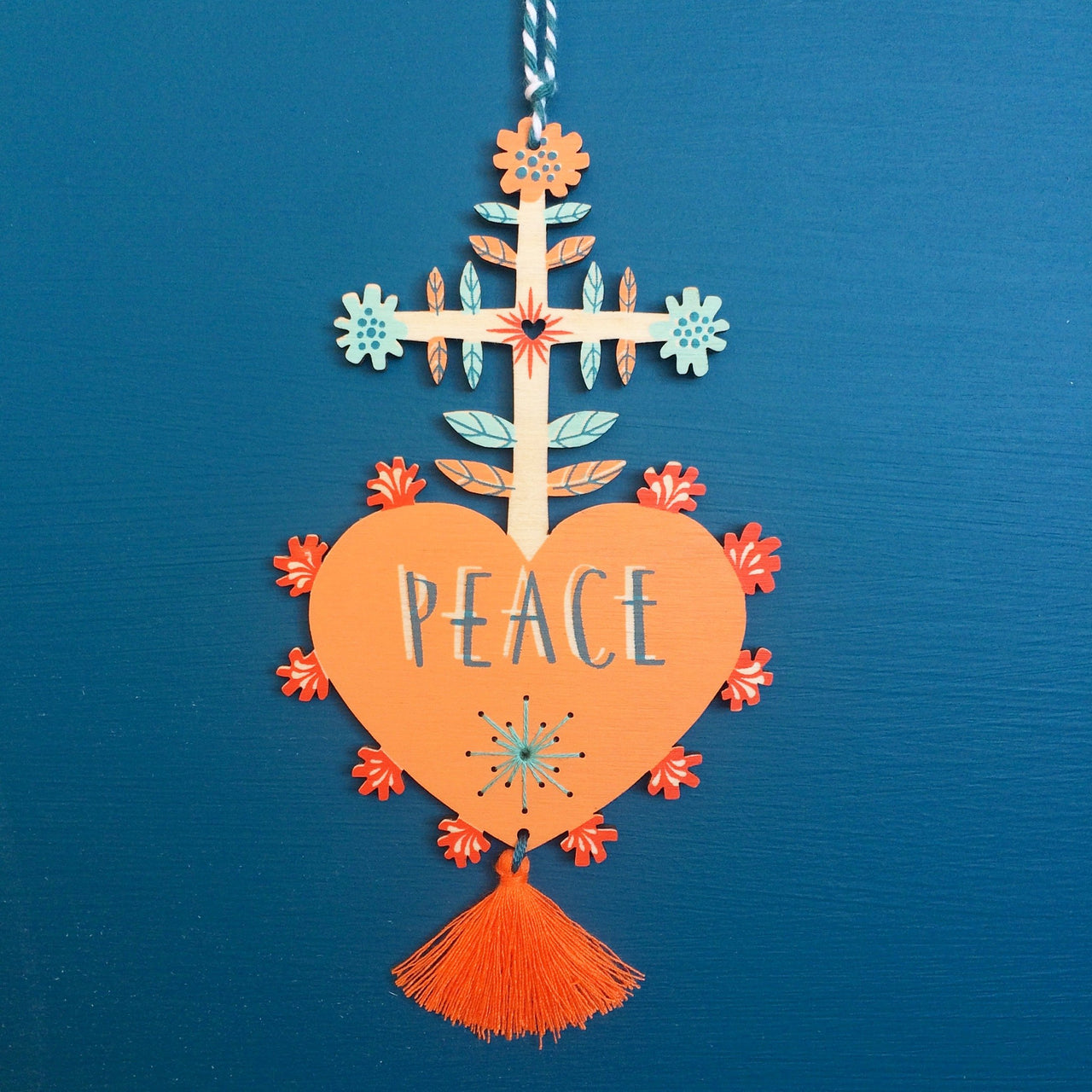 Laser cut and screen printed 'Peace' Milagro charm in apricot by Fiona Biddington aka Paper Argonauts at Soma Gallery